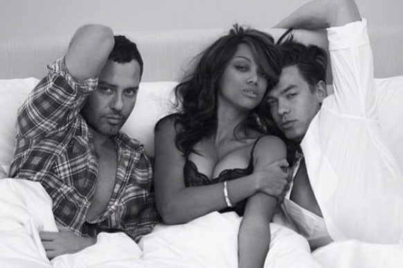 Three's a crowd? Much like Miley's sexy shot, Tyra Banks finds herself in an erm, compromising position with two mega-hotties.